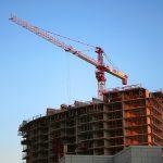 Imagem de andaime em cima de prédio em construção.