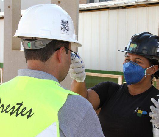 Mulher de capacete de proteção medindo a temperatura corporal de trabalhador da construção civil.